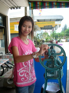 Dow operating the ice shaving machine for the Nam Khang Sai that she sells outside her boyfriends internet cafe.